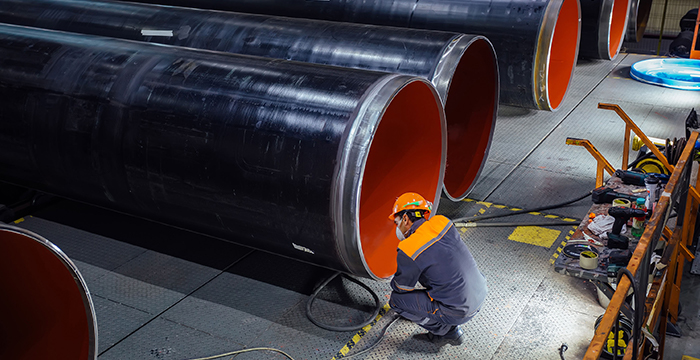 Inspector examining new coated pipe in factory.