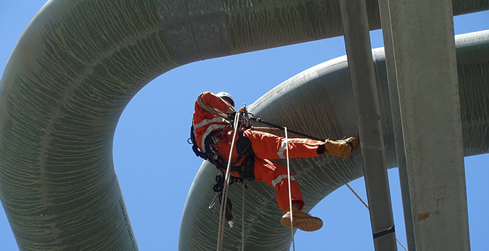 ALS technician conducting a rope access inspection from industrial piping.