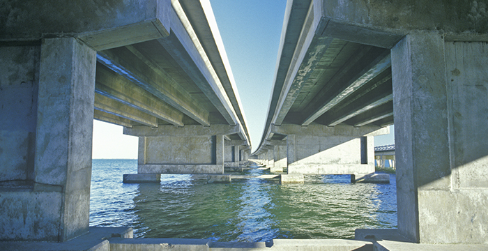 Cable-stayed concrete bridge over water.