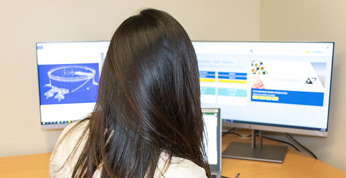 Woman sitting in front of computer screens